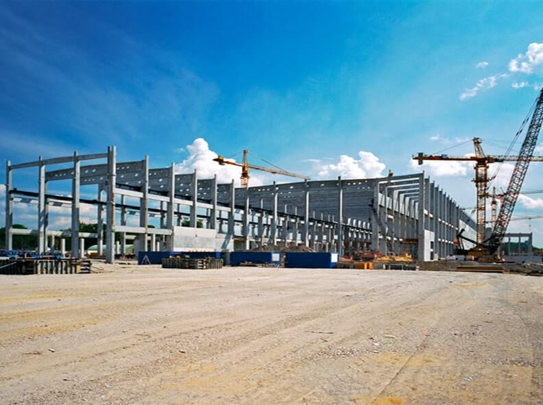 Heavy industrial cranes constructing a commercial building frame